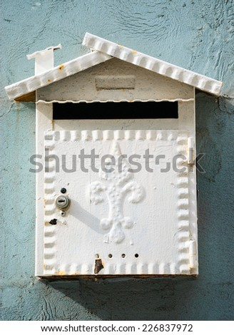 Ornate white letterbox in shape of the house with chimney decorated with Fleur De Lys on turquoise stone wall.  (Tel Aviv-Jaffa, Israel) - stock photo