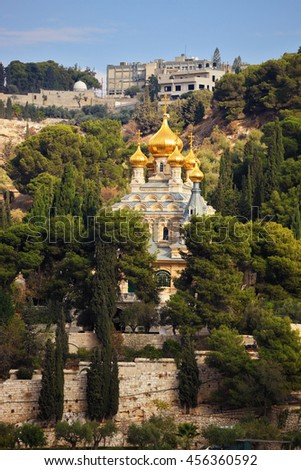 Orthodox Church of Mary Magdalene in Jerusalem. Golden domes topped with a gold cross in the green park - stock photo