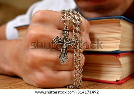 Orthodox cross in a strong hand - stock photo
