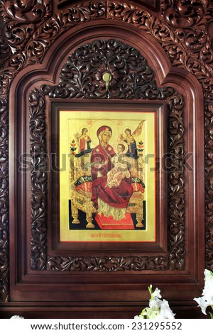 Orthodox wooden icon of the Mother of God with baby Jesus in a beautiful carved wooden salary - stock photo