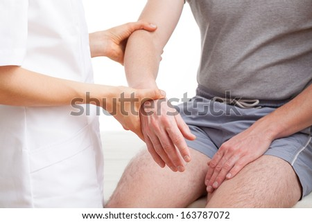 Orthopedist examining injured  arm of man in middle age