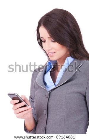 ortrait of a happy young business woman texting from her cellphone against white background - stock photo