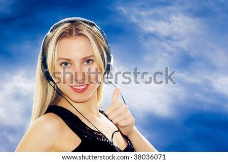 ortrait of happiness sexy young women with beautiful face in headphones and listening music on the sky background