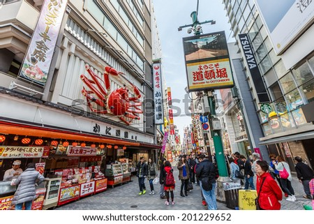 OSAKA -APRIL 7: Tourists visit Dotonbori on April 7, 14 in Osaka. It is one of the principal tourist destinations in Osaka, Japan. It is a single street, running alongside the Dotonbori canal.