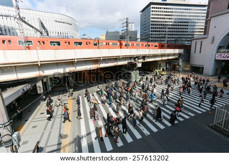 OSAKA - FEBUARY 9: People walk across the street at Osaka station on FEBUARY 9 2015 in Osaka. It is a city in the Kansai region of Japan's main island of Honshu - stock photo