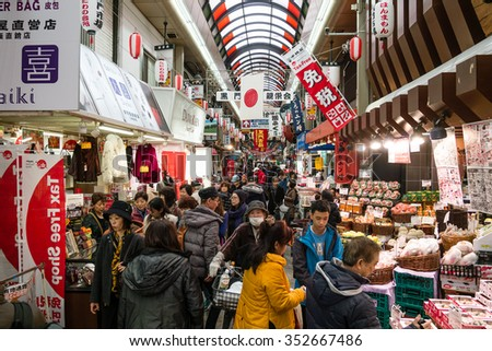 """Osaka Japan December 16,2015 : Many people are shopping at Kuromon Ichiba Market .With more than 190 years of history and tradition a very popular area known by locals as """"Osaka' s Kitchen"""". - stock photo"""