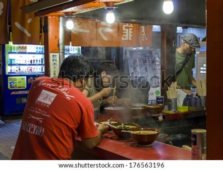 Osaka, Japan - June 20, 2010: Customers of a ramen street bar in Dohtombori entertainment district on June 20, 2010. Ramen shops are extremely popular in Japan. - stock photo