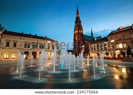 OSIJEK, CROATIA - JUNE 6, 2012: Main city square with fountain and tall cathedral at dusk. - stock photo