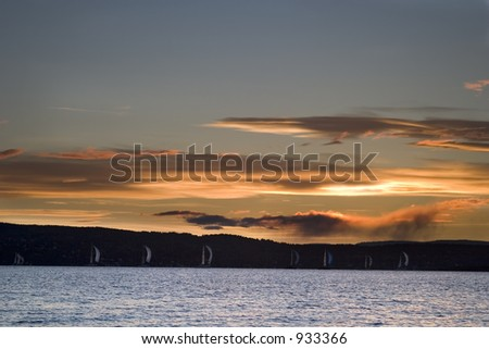 Oslo Fjord at sunset with sail boats on the horizon - stock photo