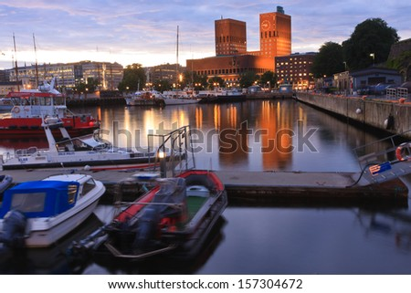 OSLO, NORWAY- AUGUST 10 2011: The Oslo cityscape dominated by twin towers reflecting in the the harbor sea water in the blue hour of the late summer evening.  - stock photo