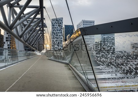 OSLO, NORWAY - DECEMBER 31, 2014: New apartment blocks and a walkway leading to the 'Barcode buildings' development which is a former dock and industrial land in central Oslo.area of Oslo, Norway. - stock photo