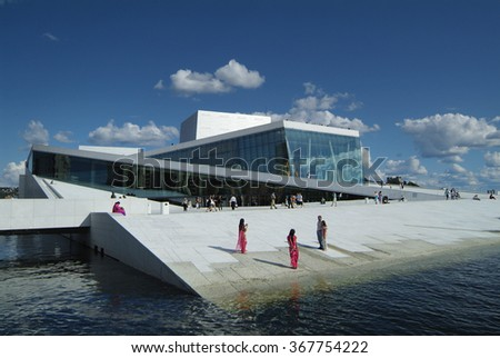 OSLO, NORWAY - JUNE 21: Unidentified tourists sightseeing around the New Opera building and new landmark on sea shore, on June 21, 2009 in Oslo, Norway