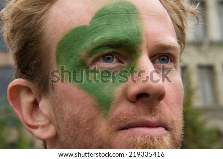 OSLO - SEPTEMBER 21: A man has a green heart painted on his face as thousands march through downtown Oslo, Norway, to support action on global climate change, September 21, 2014.  - stock photo