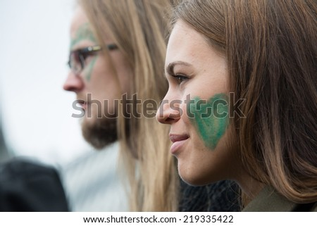 OSLO - SEPTEMBER 21: A woman and man with green hearts painted on their faces join thousands marching through downtown Oslo, Norway, to support action on global climate change, September 21, 2014.  - stock photo