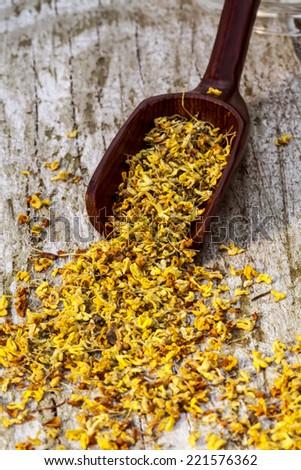 """Osmanthus """"Fragrant Flower"""" Tea supplement in black wooden scoop - stock photo"""