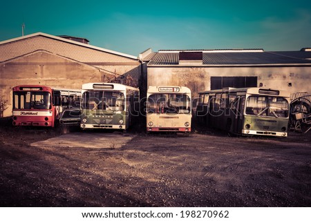 OSNABRUECK, GERMANY - NOVEMBER 2011: Photo of four Schoolbusses on a junkyard in afternoon sunlight. Applied photo filter: Sky saturation,  color temperature  - stock photo