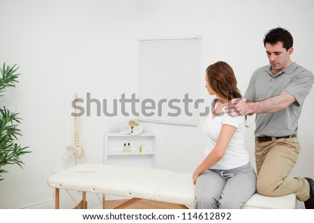 Osteopath looking at the back of a woman in a medical room - stock photo
