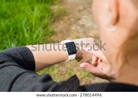 OSTFILDERN, GERMANY - APRIL 26, 2015: A middle aged Caucasian woman is checking her Apple Watch displaying the home screen with a reminder of a current meeting in her calendar while walking on a path - stock photo