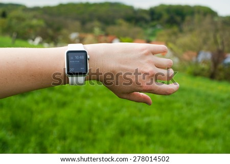 OSTFILDERN, GERMANY - APRIL 26, 2015: A middle aged Caucasian woman is checking her Apple Watch displaying the home screen with a reminder of a current meeting in her calendar while walking in the - stock photo
