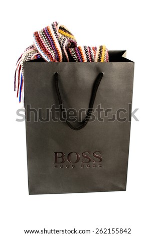 OSTFILDERN, GERMANY - MARCH 14, 2015: A black Hugo Boss shopping bag with a colourful scarf hanging out of it with shadow and reflection on a white background on March 14, 2015 in Ostfildern, Germany - stock photo