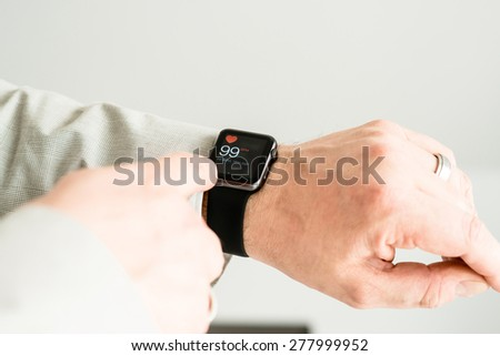 OSTFILDERN, GERMANY - MAY 14, 2015: A businessman is checking his pulse using his black Apple Watch Sport. The Apple Watch is the latest device by computer and smartphone manufacturer Apple Computer - stock photo