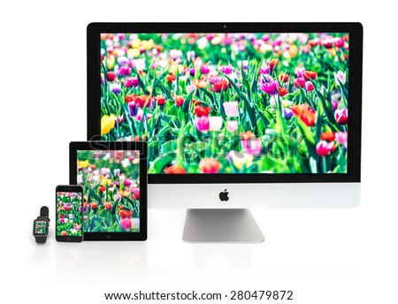 OSTFILDERN, GERMANY - MAY 21, 2015: A collection of Apple devices: Apple watch, iPhone 6, iPad 2 and iMac 27 inch. All devices are displaying different sections of the same photo of a tulip field - stock photo