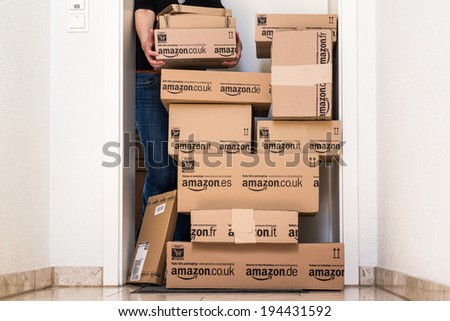OSTFILDERN-SCHARNHAUSEN, GERMANY - MAY 18, 2014: A woman is picking up a large stack of parcels by Amazon.com in different sizes waiting in front of the entrance door to her flat on May, 18, 2014 in - stock photo
