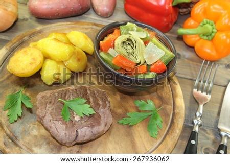 Ostrich steaks with baked potatoes and vegetables on a wooden board - stock photo