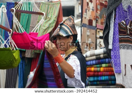 OTAVALO, ECUADOR - FEBRUARY 13, 2016: Indigenous woman in traditional dress folding a textile in the market