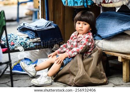 OTAVALO, ECUADOR - JAN 3, 2015: Unidentified Ecuadorian little boy at the Otavalo Market. 71,9% of Ecuadorian people belong to the Mestizo ethnic group - stock photo