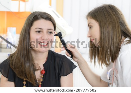 Otolaryngologist examining a woman ear in a clinic - stock photo