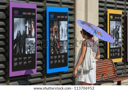 OTTAWA, CANADA - AUGUST 25: A woman reading an outdoor exhibit at the Chateau Laurier Hotel on August 25, 2012 in downtown Ottawa, Ontario. The exhibit was in honor of the Queen's Diamond Jubilee. - stock photo