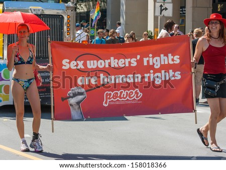 OTTAWA, CANADA - AUGUST 26: Women carrying a banner about sex workers' rights in the Capital Pride Parade on August 26, 2012 in Ottawa, Ontario.