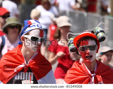 OTTAWA, CANADA – JULY 1: Two teens walking through the crowd during Canada Day on July 1, 2011 in downtown Ottawa, Ontario. Canada Day is a national holiday and is celebrated annually.