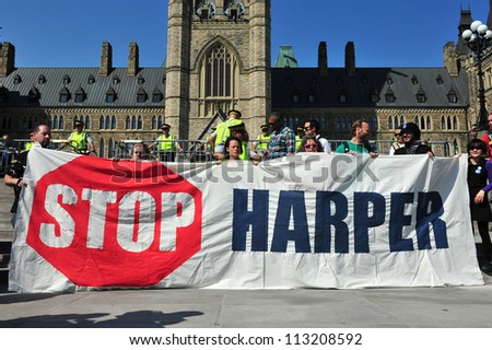 OTTAWA, CANADA - SEP 17:  Unidentified Occupy protesters hold an anti-Harper  sign at a protest to mark the anniversary of the Occupy Wall Street movement on Parliament Hill Sep 17, 2012 in Ottawa. - stock photo