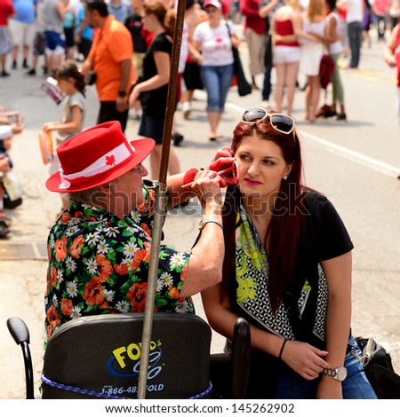 OTTAWA - JULY 1:  An unidentified lady getting a Maple Leaf painted on her face on Rideau Street during the Canada Day, a national holiday, celebrations July 1, 2013 in the Canadian capital of Ottawa - stock photo