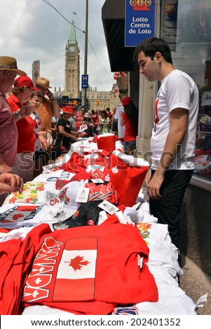 OTTAWA - JULY 1:  Vendor sells Canada related goods to the thousands of people who visit Parliament Hill for Canada Day celebrations in the national capital July 1, 2014 in Ottawa, Ontario. - stock photo