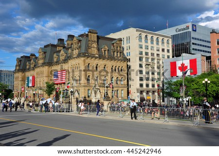 OTTAWA,JUN 29, 2016:  People gather on Wellington St to await the motorcade for Obama who was there for Three Amigos summit. The Langevin Block was covered with  Mexican and US flag for the occasion. - stock photo