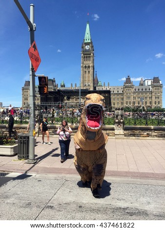 OTTAWA - JUNE 15, 2016:  Person dressed as a dinosaur visits Parliament Hill in order to promote the Ultimate Dinosaurs exhibit at the Canadian Museum of Nature.  - stock photo