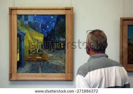 OTTERLO, NETHERLANDS - AUGUST 8, 2012: Visitor looks at the painting Cafe Terrace at Night (1888) by Vincent van Gogh in the Kroller Muller Museum in Otterlo, Netherlands.  - stock photo