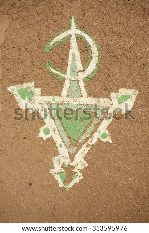 OUARZAZATE, MOROCCO, NOV 17: Moroccan white and green tribal symbol painted on a mud wall by unknown artist in Ouarzazate Morocco. 2010