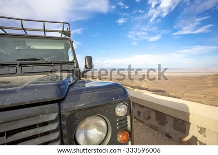 OUARZAZATE, MOROCCO, NOVEMBER 17:  Head light closeup of 4x4 Land Rover Defender with arid landscape and mountains in the background.  Morocco 2010 - stock photo