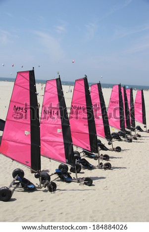 OUDDORP, THE NETHERLANDS - JULY 30TH 2013: Multiple beach sailing carts (Blokarts) with bright pink sails are standing in line on the beach in Ouddorp at the rental office on a sunny day in July.