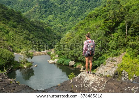 oung and beautiful girl is looking from the top of a high waterfall in Mauritius against the backdrop of scenic mountains - stock photo