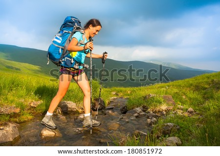 oung girl in tourist clothes with a backpack and trekking sticks jumping over a mountain stream on a green hill - stock photo