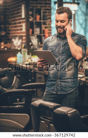 our appointment is on Monday! Cheerful young bearded man talking on mobile phone and looking at digital tablet while standing at barbershop - stock photo