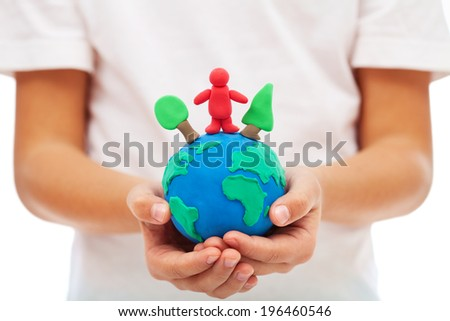 Our environment and us concept with modeling clay earth in child hands - stock photo