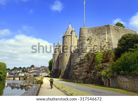 Oust river, cycling trail and the Chateau of Josselin, Brittany, France. The castle was first built in the 11th century and rebuilt at various times since - stock photo
