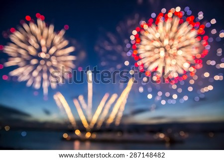 Out of focus colorful fireworks on the black sky background over-water - stock photo