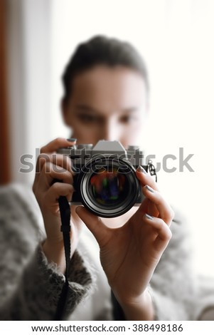out of focus girl with photo camera in her hands on sofa near window - stock photo